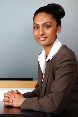 This is an image of a confident smiling business woman sitting by a table. Stock Photo