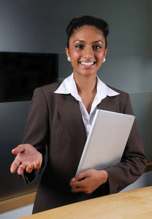 This is an image of a welcoming business woman holding a book. Stock Photo