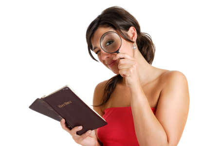 This is an image of female student studying the bible and looking through using a magnifying glass.