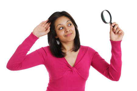 This is an image of female student looking through a magnifying glass. photo