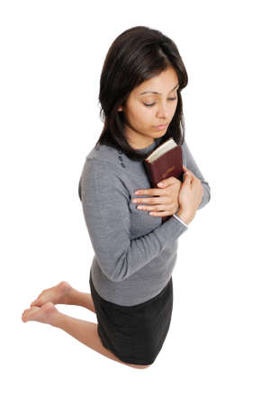 This is an image of young woman kneeling with a bible. photo