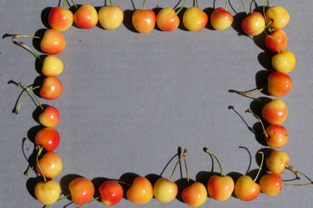 Square frame from fruits, from bright yet ripe cherries