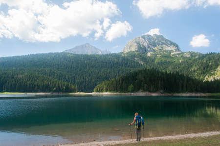 Žabljak, Montenegro - 08.21.2016: Mountains over black lake in Durmitor National Park.