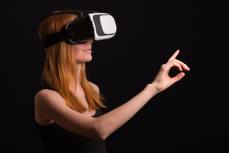 Studio portrait of young redhead girl playing with virtual reality goggles for mobile game application