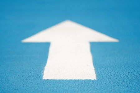 White arrow on blue running track with soft focus
