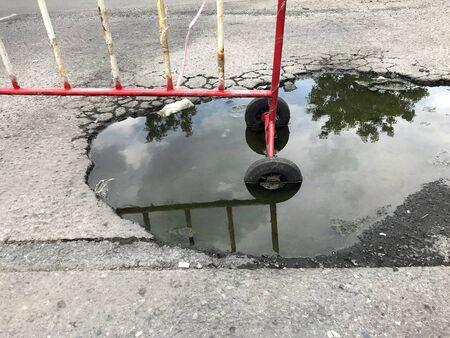 Broken asphalt road with water, No passing zone Imagens