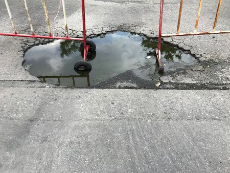 Broken asphalt road with water, No passing zone