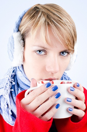 Winter portrait of a girl who holds cup of hot chocolate. Image has clipping path.