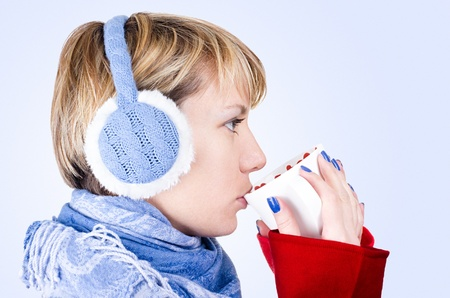 Blond girl dressed in winter clothes drinks a tea. Image has clipping path.
