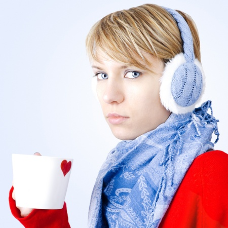 Blond girl dressed in winter clothes holds cup of tea. Image has clipping path.