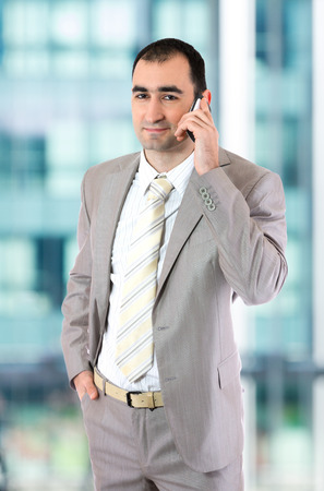 Young handsome businessman talking on a phone.