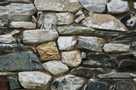 Stone wall texture. Serbian rural house wall made of natural stones background. Close up on stone wall surface.