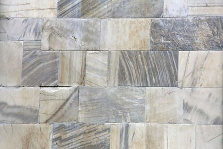 Natural marble stone wall. Wall of fine stone tiles for wallpaper. 12th century marble cubes.