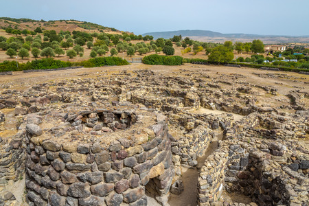 consisting: BARUMINI,ITALY - SEPTEMBER 20,2014 - View at the ruins from Su Nuraxi nuraghe near Barumini in Sardinia.Su Nuraxi is a settlement consisting by a Nuraghe, dating from the seventeenth century BC. Stock Photo