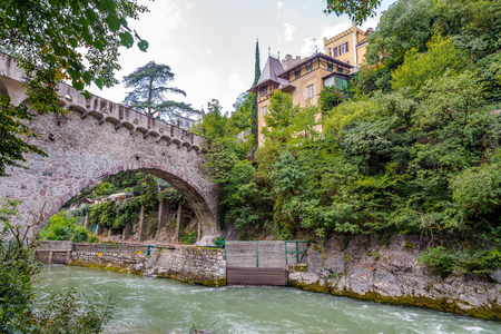september 2: MERANO,ITALY - SEPTEMBER 2,2015 - Stone bridge over Passer river in Merano. Merano is a town and commune in South Tyrol, northern Italy.