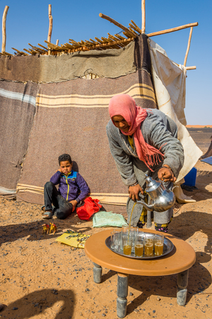 Merzouga, Morocco - APRIL 4.2017 - Nomads Living in the area of ??Merzouga. A nomad is a member of a community of people WHO live in different locations, moving from one place to Another. Stock Photo - 77283679