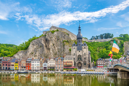 View at the embankment of Meuse river with houses and church of Our Lady Assumption in Dinant, Belgium