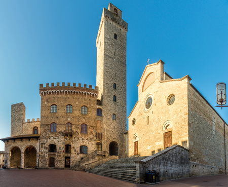 View at the Cathedral of Santa Maria Assunta with Town hall building at the Place of Duomo in San Gimignano, Italy Archivio Fotografico