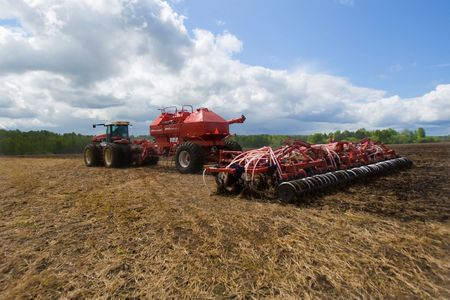seeding: Red seeder working in the clear field