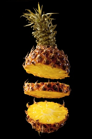 Pineapple on a black background cut on three parts