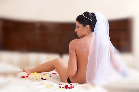 nude girl in veil sitting on the bed with his back to the camera photo