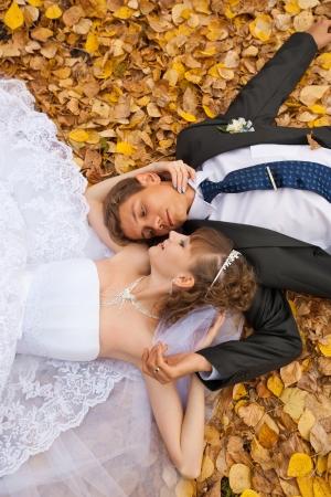 bröllop tema, bruden och brudgummen är i lönnlöv på gräs