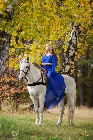 Young girl riding a white horse in the autumn park photo