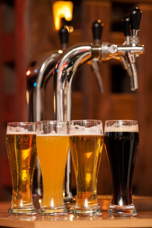 tavern: Four glasses of beer against beer tap Stock Photo