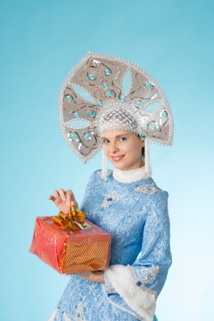 snow maiden in a blue clothing with a red gift in hands photo