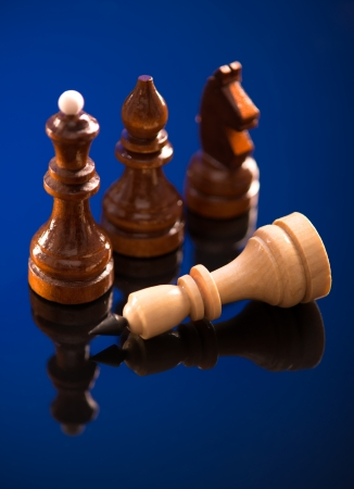 office politics: A conceptual composition of chess pieces standing over defeated king on reflective surface