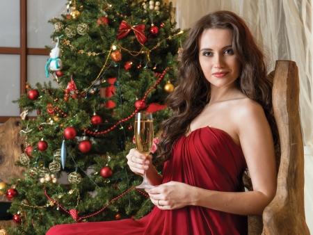 flicka med ett glas champagne i handen på bakgrund nyår träd