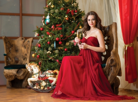 girl with a glass of champagne in hand on background of New Year tree photo