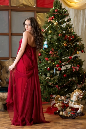 girl in red on background of New Year tree photo