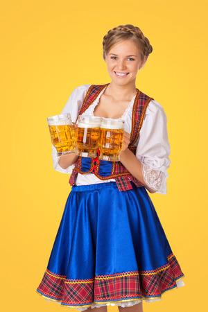 dirndl dress: Young sexy Oktoberfest woman wearing a traditional Bavarian dress dirndl serving beer mugs