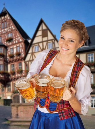 Young sexy Oktoberfest woman wearing a traditional Bavarian dress dirndl serving beer mugs photo