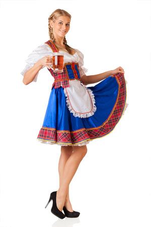 Young sexy Oktoberfest woman wearing a traditional Bavarian dress dirndl serving beer mugs