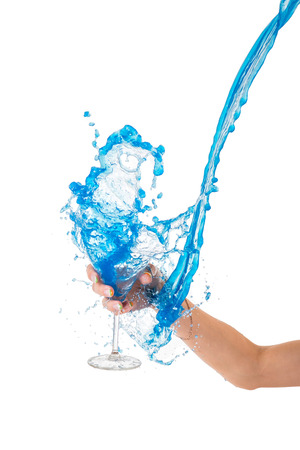 overflowing: Blue water splashing in glass held by hand, white background