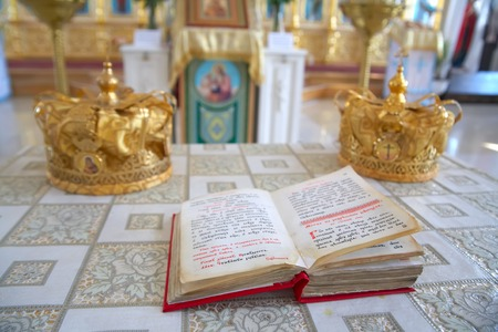 bible altar: Orthodox wedding ceremonial crowns and the Bible on the altar, ready for a crowning ceremony. Stock Photo