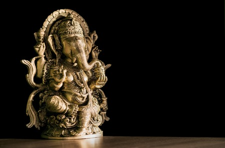 Beautiful figurine of Hindu god of wisdom, knowledge and new beginnings Ganesha against dark background.