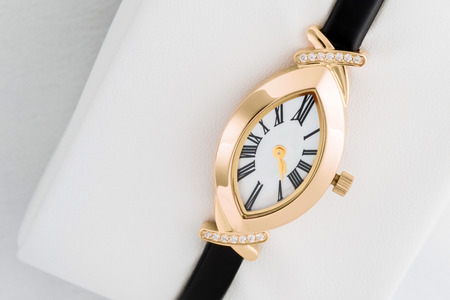 elegant ladies gold watch with a black leather strap Stock Photo