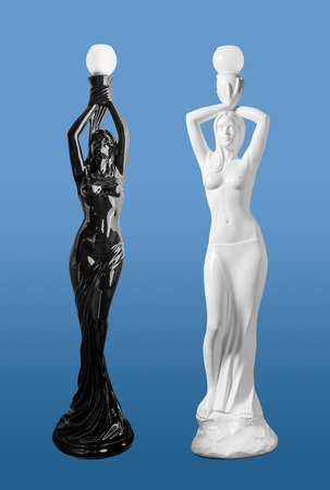 OpposTwo ancient lighting statuettes of women holding bulbs above their heads on blue background.