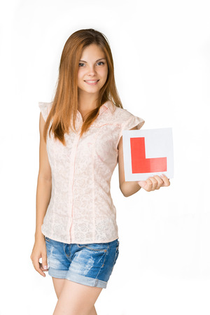 pass test: Young happy learner driver holding L-plate, proud of passing her driving test at school. Stock Photo