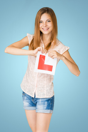 Young happy learner driver holding L-plate, proud of passing her driving test at school. Stock Photo