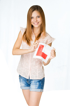 pass test: Young happy learner driver tearing L-plate after passing her driving test at school successfully.