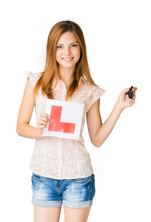 learner: Young teenage learner driver holding L-plate and car keys, proud of passing her driving test at school. Stock Photo