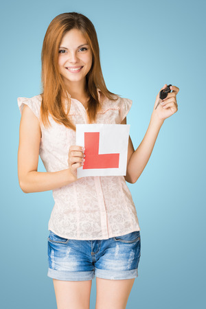 l plate: Young teenage learner driver holding L-plate and car keys, proud of passing her driving test at school. Stock Photo