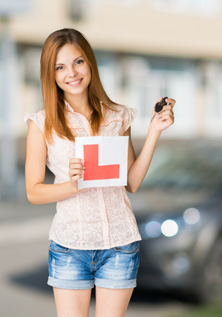 pass test: Young teenage learner driver holding L-plate and car keys, proud of passing her driving test at school. Stock Photo