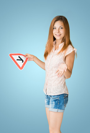 Young teenage learner driver holding U-plate (russian analogue L-plate) and car keys, proud of passing her driving test at school.