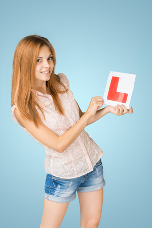 learner: Young happy learner driver holding L-plate, proud of passing her driving test at school. Stock Photo