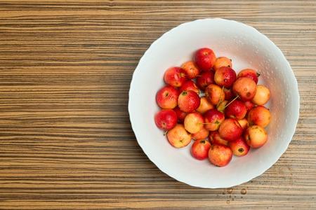 Close-up of wild cherries, Prunus avium, in bowl on wooden table.